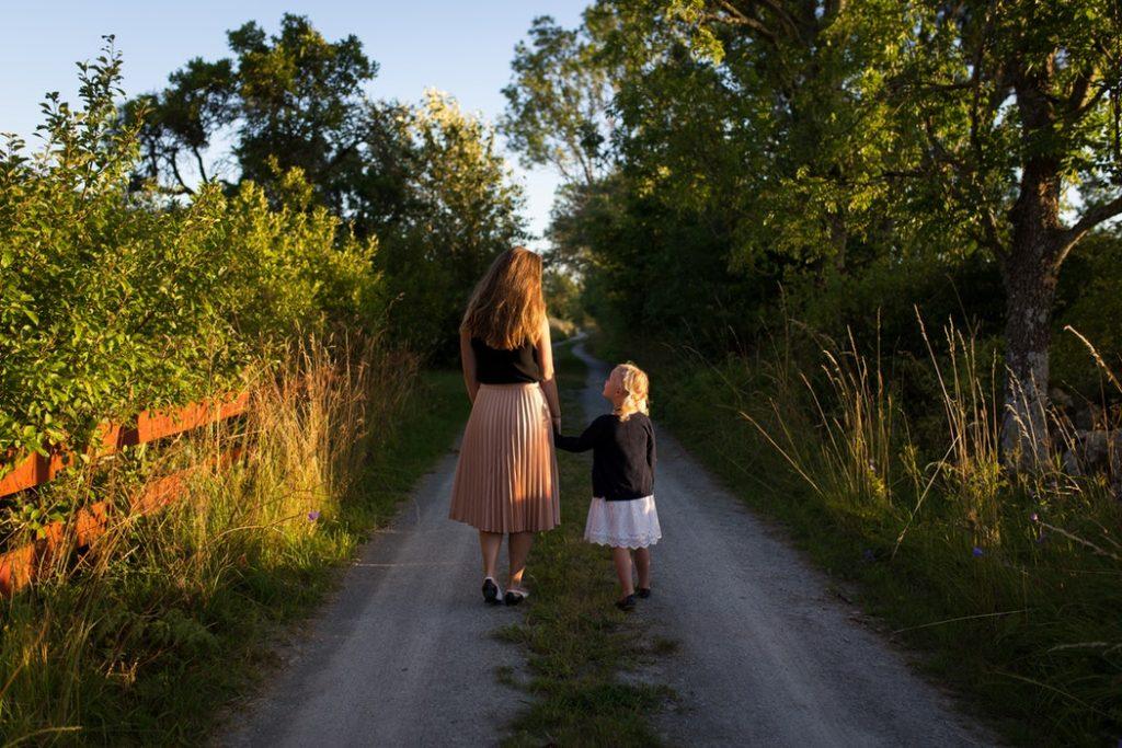 madre y niña de espaldas en un camino de campo